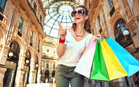 Discover most unexpected trends in Milan. Portrait of smiling fashion monger in eyeglasses with colorful shopping bags in Galleria Vittorio Emanuele II pointing on something Zdjęcie Seryjne