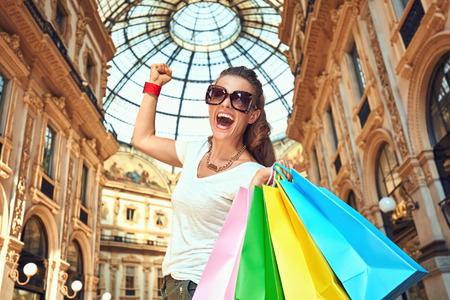 rejoicing: Discover most unexpected trends in Milan. Happy fashion woman in eyeglasses with colorful shopping bags in Galleria Vittorio Emanuele II rejoicing Stock Photo