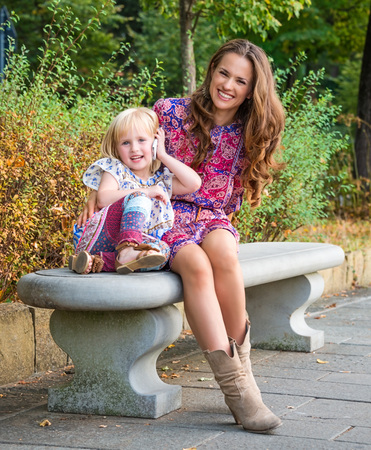citypark: Outdoors lounge. Happy mother and daughter talking cellphone while sitting on the bench at the park. Stock Photo