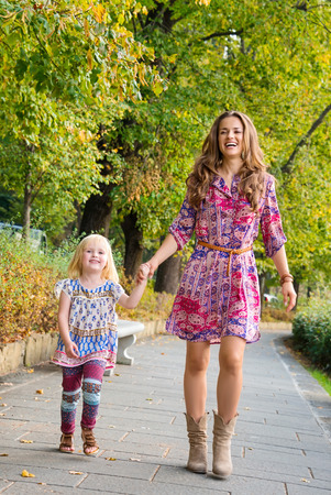 citypark: Outdoors lounge. Full length portrait of happy mother and daughter walking at the park.