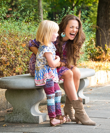 Outdoors lounge. Happy mother and daughter having fun time while sitting on the bench at the park.