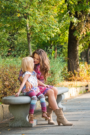 Outdoors lounge. Happy mother and daughter sitting on the bench at the park.