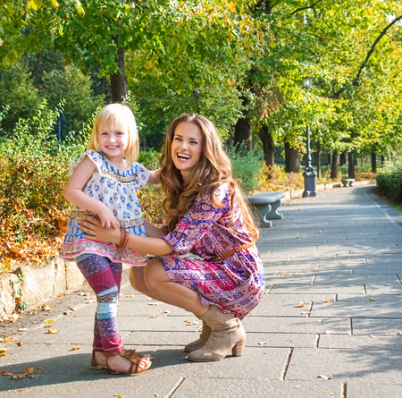 citypark: Outdoors lounge. Full length portrait of happy mother and daughter at the park. Stock Photo