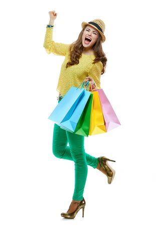 rejoicing: Colourful shopping vibes. Full length portrait of happy brunette woman in hat and bright clothes with colorful shopping bags rejoicing on white background Stock Photo