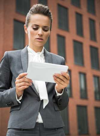 topicality: The new business. Portrait of modern business woman against office building using tablet PC