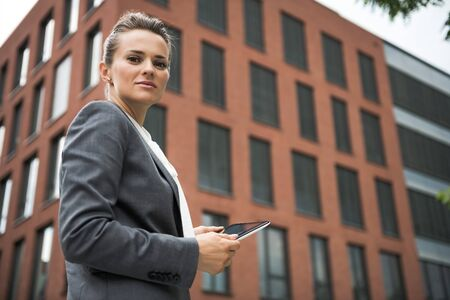 The new business. Portrait of modern business woman with tablet PC against office building