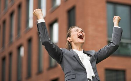 rejoicing: The new business. Happy modern business woman against office building rejoicing