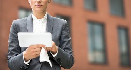 topicality: The new business. Modern business woman using tablet PC against office building Stock Photo