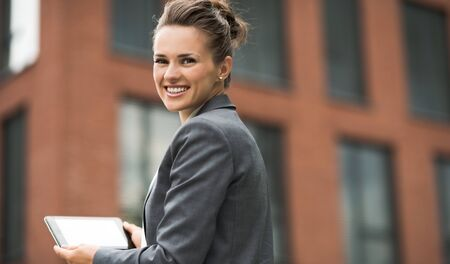 topicality: The new business. Smiling modern business woman against office building using tablet PC Stock Photo