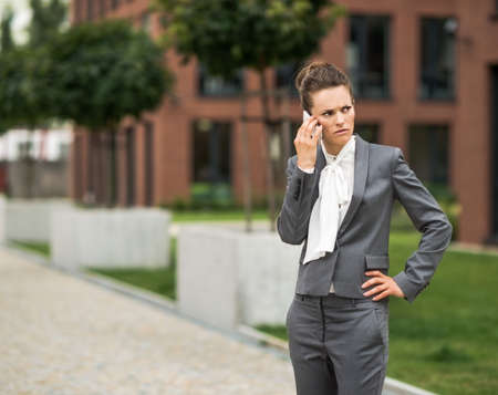 disquieted: The new business. Concerned modern business woman talking cellphone at the office district