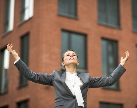 exhilaration: The new business. Relaxed modern business woman against office building rejoicing