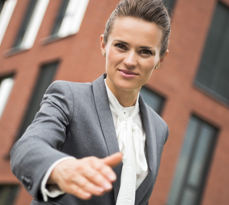 handclasp: The new business. Portrait of modern business woman stretching hand for handshake against office building