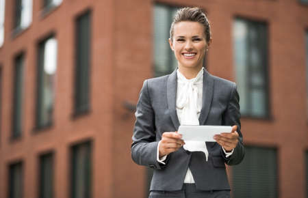 The new business. Smiling modern business woman using tablet PC against office building