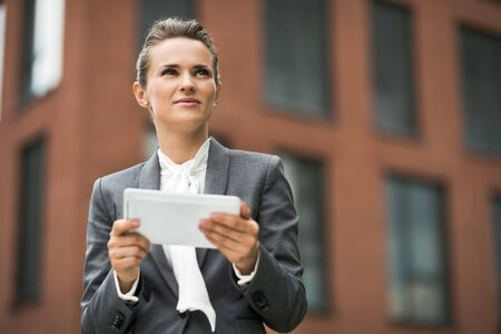 The new business. Modern business woman with tablet PC against office building