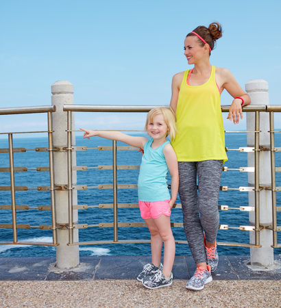 Look Good, Feel great! Full length portrait of happy mother and child in fitness outfit on embankment pointing on something Stock Photo
