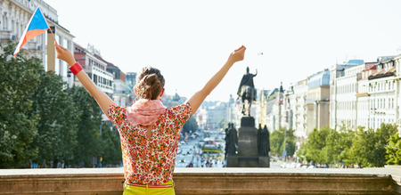 Catch the spirit of old Europe in Prague. Seen from behind young woman with Czech flag rejoicing near National Museum at Wenceslas Square Stock Photo