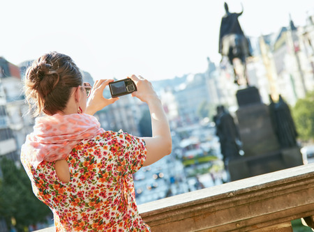 czech women: Catch the spirit of old Europe in Prague. Seen from behind young woman taking photos with digital camera standing near National Museum at Wenceslas Square