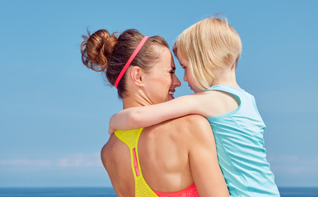 Look Good, Feel great! Seen from behind mother and child in fitness outfit hugging on embankment Stock Photo
