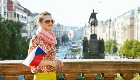 Catturare lo spirito della vecchia Europa a Praga. Sorridente giovane donna in occhiali da sole con la bandiera ceca in piedi vicino al Museo Nazionale a Piazza Venceslao e guardando in lontananza