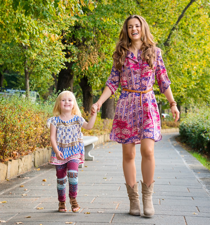 Outdoors lounge. Full length portrait of happy mother and daughter walking at the park.