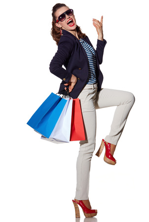 the french way: Luxury Shopping. The French way. Full length portrait of cheerful young woman with shopping bags in sunglasses posing on white background Stock Photo