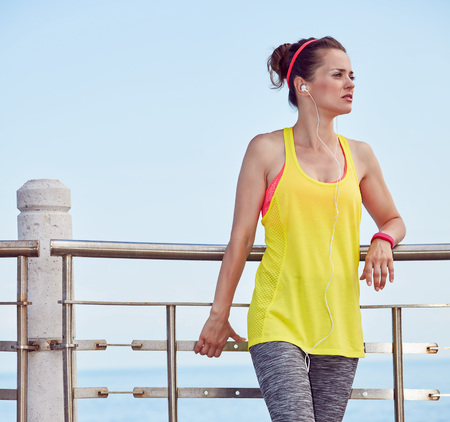 Look Good, Feel great! young woman in fitness outfit looking into the distance at the embankment Stock Photo