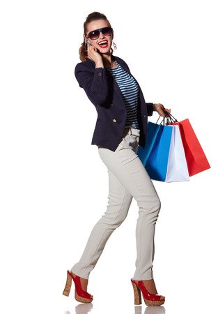 the french way: Luxury Shopping. The French way. Full length portrait of happy young woman with shopping bags in sunglasses talking on a smartphone and walking isolated on white