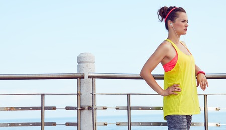 Look Good, Feel great! young woman in fitness outfit looking into the distance and listening to the music at the embankment
