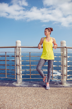 Look Good, Feel great! Full length portrait of Relaxed young healthy woman in fitness outfit looking into the distance at the embankment Stock Photo