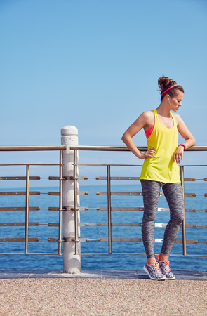 Look Good, Feel great! Full length portrait of young athlete in fitness outfit relaxing after workout at the embankment