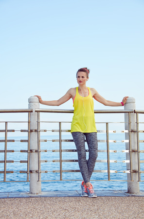 Look Good, Feel great! Full length portrait of young woman in fitness outfit looking aside at the embankment Stock Photo