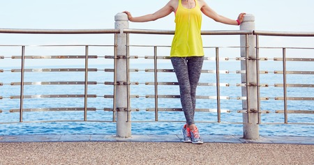 Look Good, Feel great! Closeup on young woman in fitness outfit relaxing after workout at the embankment Stock Photo