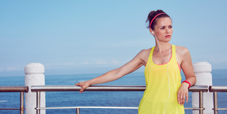Look Good, Feel great! young healthy woman in fitness outfit looking aside and listening to the music at the embankment Stock Photo