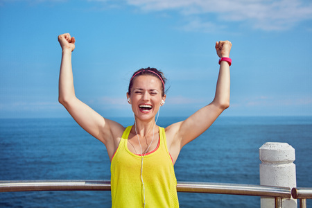Look Good, Feel great! Portrait of Smiling young athlete in fitness outfit rejoicing at the embankment Stock Photo