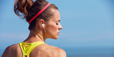 Look Good, Feel great! Portrait of young healthy woman in fitness outfit listening to the music at the embankment