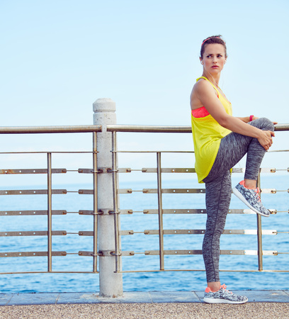 Look Good, Feel great! Full length portrait of young woman in fitness outfit looking aside and stretching at the embankment Stock Photo