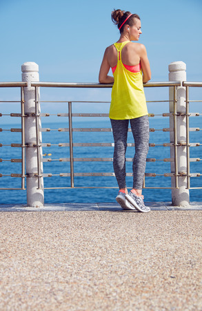 Look Good, Feel great! Seen from behind young healthy woman in fitness outfit looking aside at the embankment