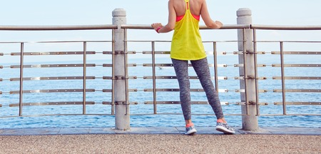 sport fitness: Look Good, Feel great! Closeup on young woman in fitness outfit standing at the embankment Stock Photo