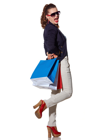 the french way: Luxury Shopping. The French way. Full length portrait of cheerful young woman with shopping bags in sunglasses having fun time on white Stock Photo