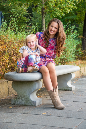 Outdoors lounge. Happy mother and daughter talking cellphone while sitting on the bench at the park. Stock Photo