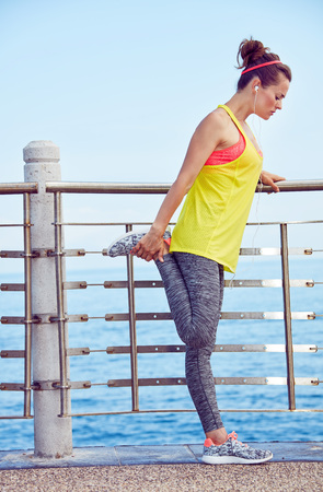Look Good, Feel great! Full length portrait of young woman in fitness outfit stretching at the embankment