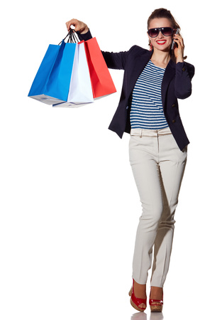 french way: Luxury Shopping. The French way. Full length portrait of smiling young woman in sunglasses talking on a smartphone and showing shopping bags isolated on white