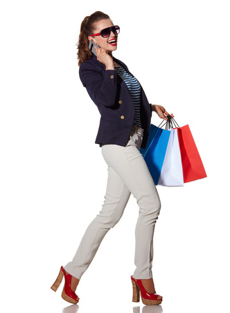 the french way: Luxury Shopping. The French way. Full length portrait of happy young woman with shopping bags in sunglasses speaking on a mobile phone and walking isolated on white Stock Photo