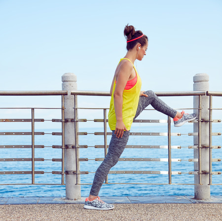 Look Good, Feel great! Full length portrait of young healthy woman in fitness outfit stretching at the embankment