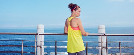 Look Good, Feel great!  Seen from behind young athlete in fitness outfit standing at the embankment Stock Photo