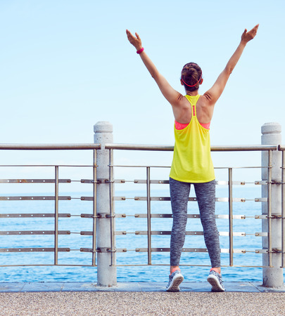 rejoicing: Look Good, Feel great! Seen from behind relaxed young healthy woman in fitness outfit rejoicing at the embankment Stock Photo
