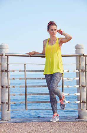 Look Good, Feel great! Full length portrait of young woman in fitness outfit looking into the distance and listening to the music at the embankment