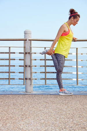 Look Good, Feel great! Full length portrait of young athlete in fitness outfit stretching at the embankment
