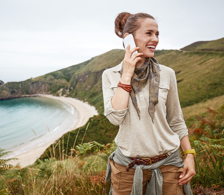 Into the wild in Spain. Portrait of happy healthy woman hiker looking aside and using a mobile phone in front of ocean view landscape