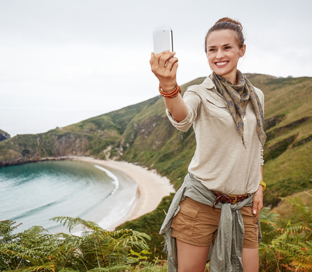 Into the wild in Spain. smiling healthy woman hiker taking selfie with smartphone in front of ocean view landscape